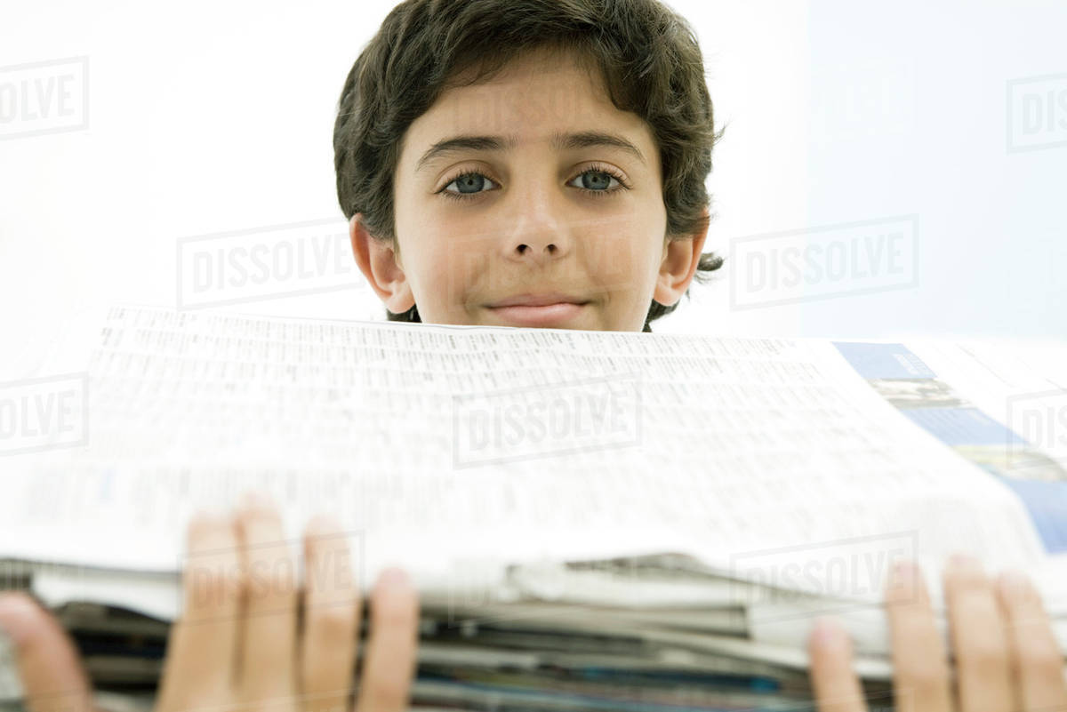 boy holding tall stack of newspapers, smiling at camera - stock