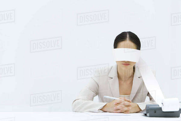 Woman sitting at table with adding machine tape wrapped around her eyes Royalty-free stock photo
