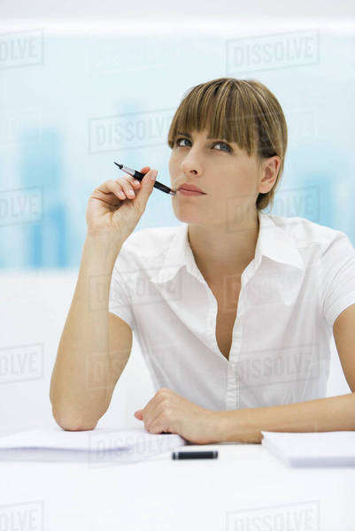 Woman looking up and holding pen up to her cheek Royalty-free stock photo