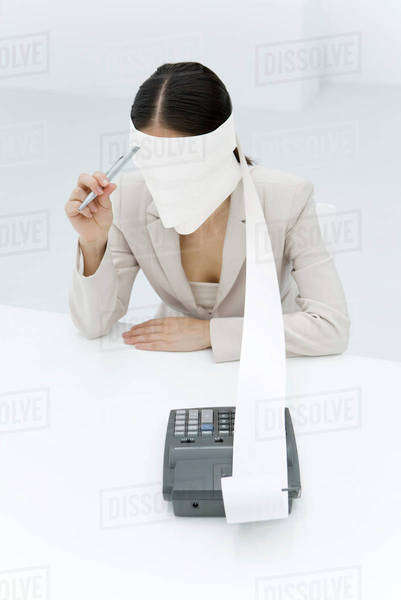 Woman sitting with adding machine tape wrapped around head, holding pen to forehead Royalty-free stock photo