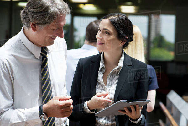 Business professionals marvelling at features of new digital tablet Royalty-free stock photo