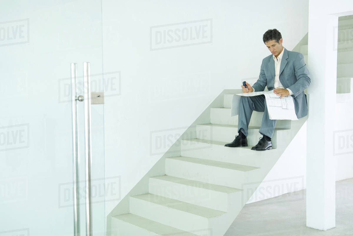 Man Sitting On Stairs Looking At Blueprints Stock Photo Dissolve