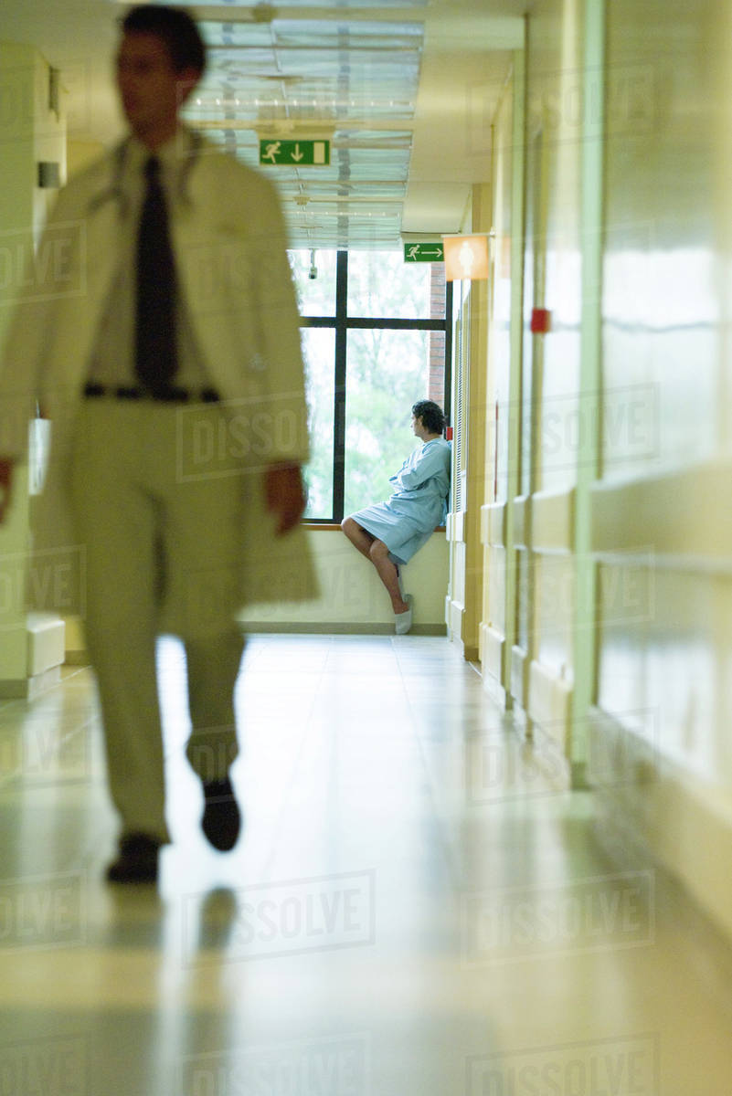 Man sitting, looking out window, wearing hospital gown, doctor ...