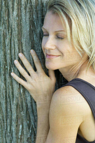 75f540b56a26d7 Woman leaning against tree trunk