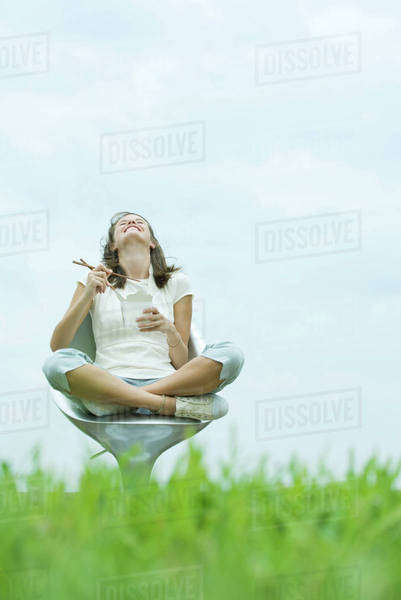 Teen girl sitting eating Chinese takeout, head back, low angle view Royalty-free stock photo
