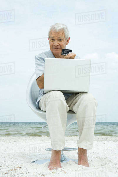 Senior man making credit card purchase online, holding up credit card, sitting in chair on beach Royalty-free stock photo