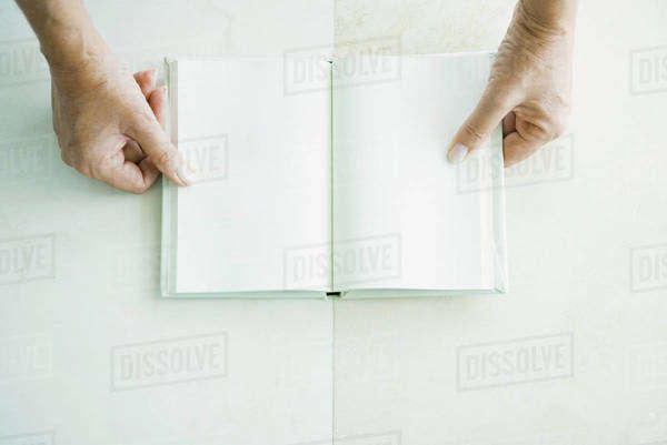 Cropped view of hands holding open book, viewed from directly above Royalty-free stock photo