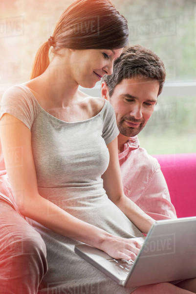Couple relaxing together on sofa with laptop computer Royalty-free stock photo