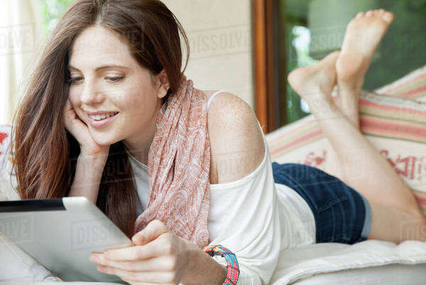Young woman lying on stomach, looking at digital tablet Royalty-free stock photo