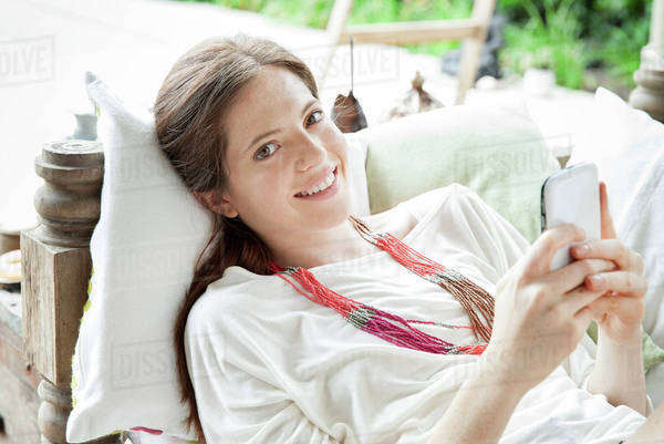 Young woman lying on back with smartphone in hands, portrait Royalty-free stock photo