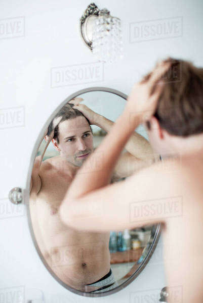 Man examining hairline in mirror Royalty-free stock photo