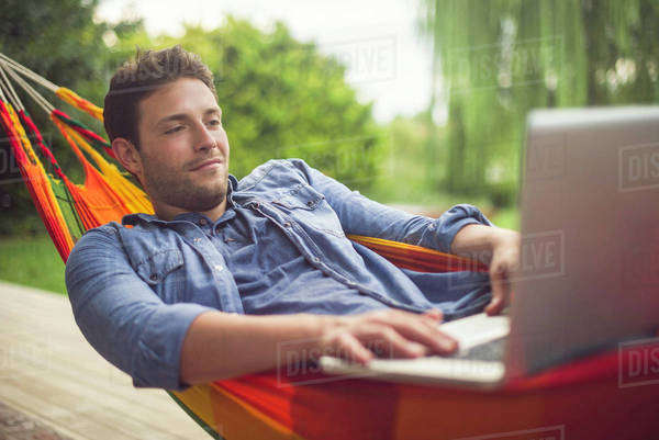 Man reclining in hammock using laptop computer Royalty-free stock photo