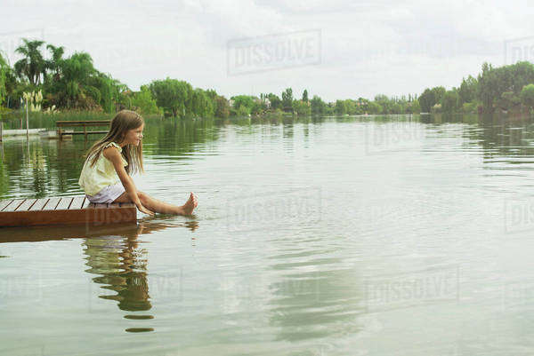 Girl sitting on dock with feet dangling in lake, portrait Royalty-free stock photo