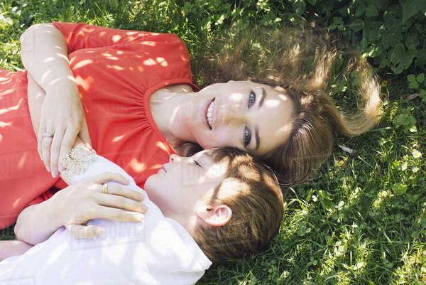 Mother and boy lying on grass Royalty-free stock photo