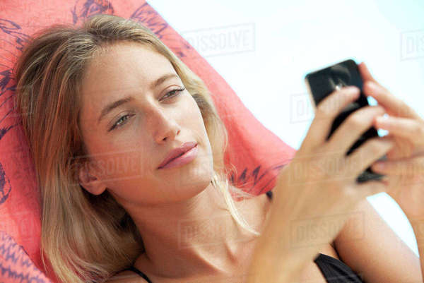 Woman relaxing on lounge chair using smartphone Royalty-free stock photo