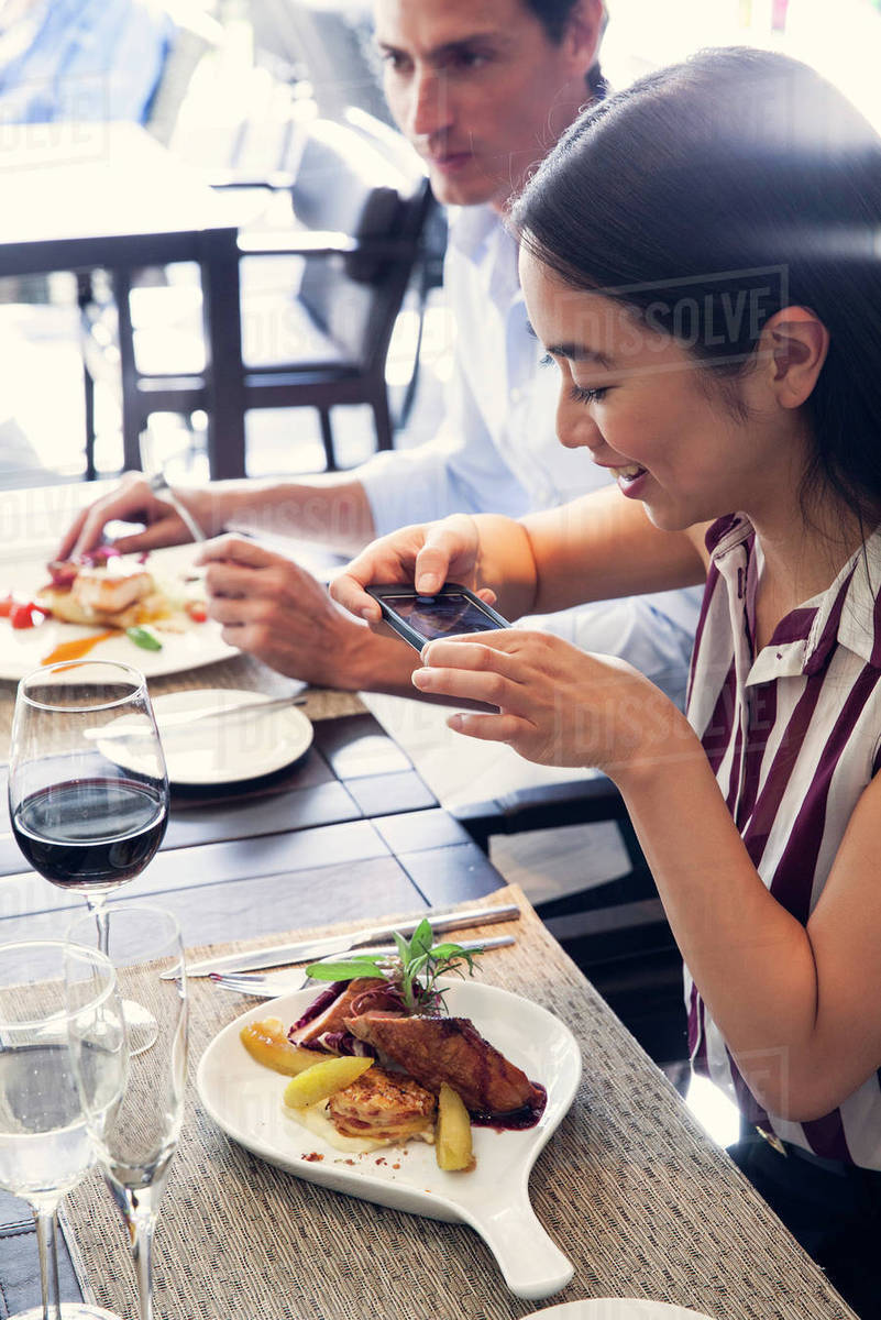 Woman using smarphone to photograph her meal in restaurant Royalty-free stock photo