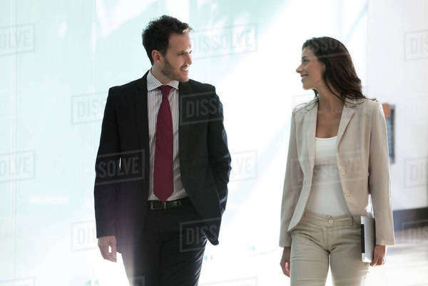 Colleagues chatting while walking together in office Royalty-free stock photo