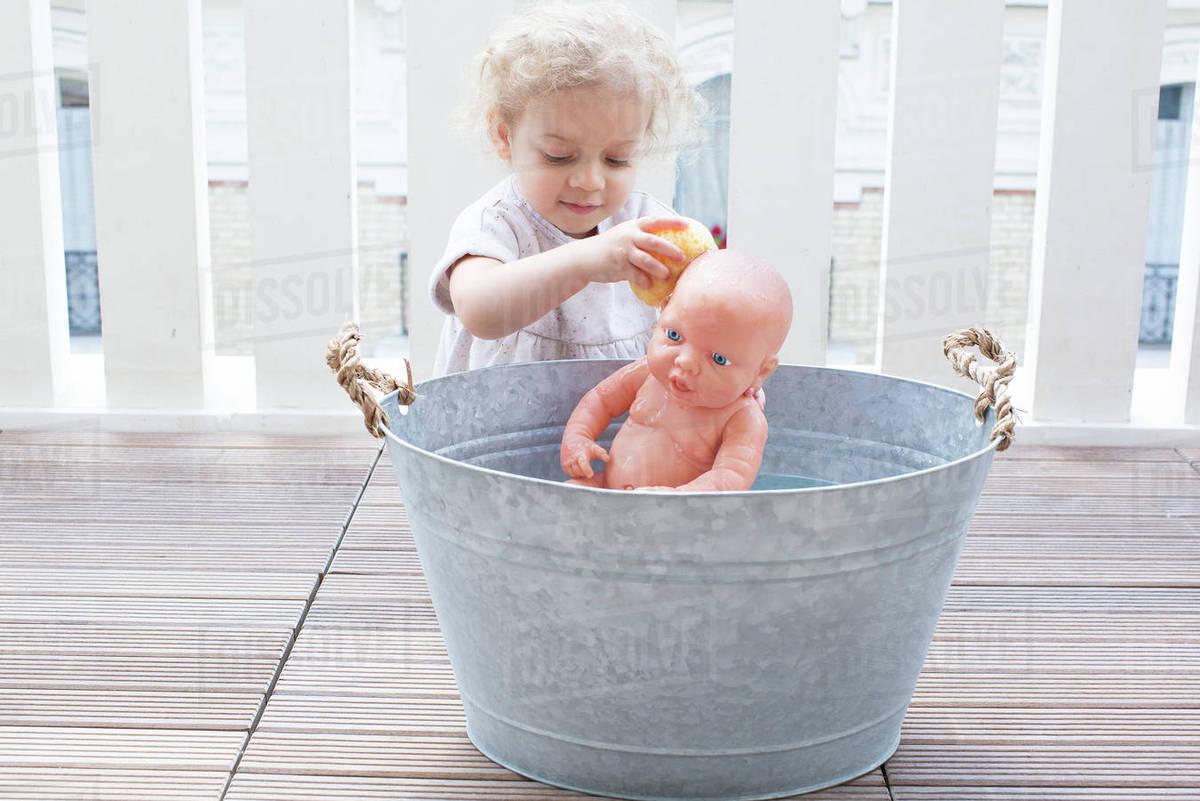 Little girl bathing baby doll in bucket outdoors - Stock Photo ...