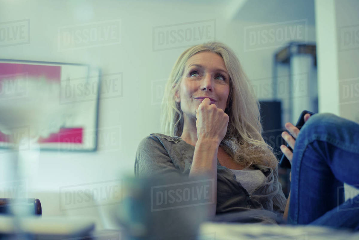 Mature woman using smartphone at home Royalty-free stock photo