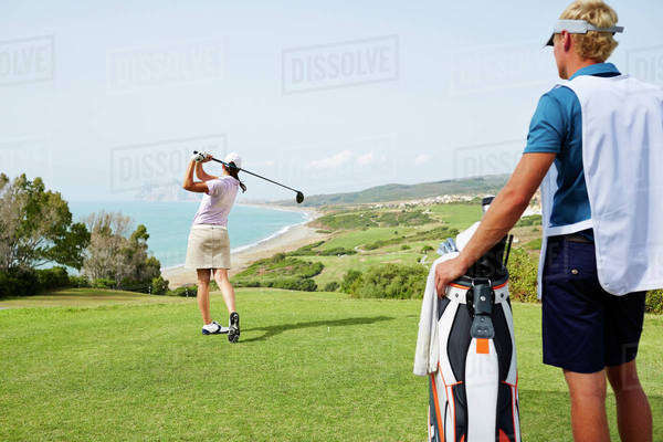 Caddy watching woman tee off on golf course overlooking ocean Royalty-free stock photo