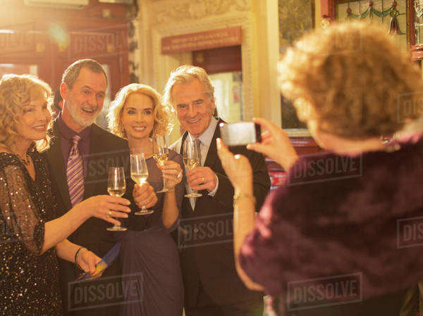 Woman photographing well dressed couples toasting champagne glasses in theater lobby Royalty-free stock photo