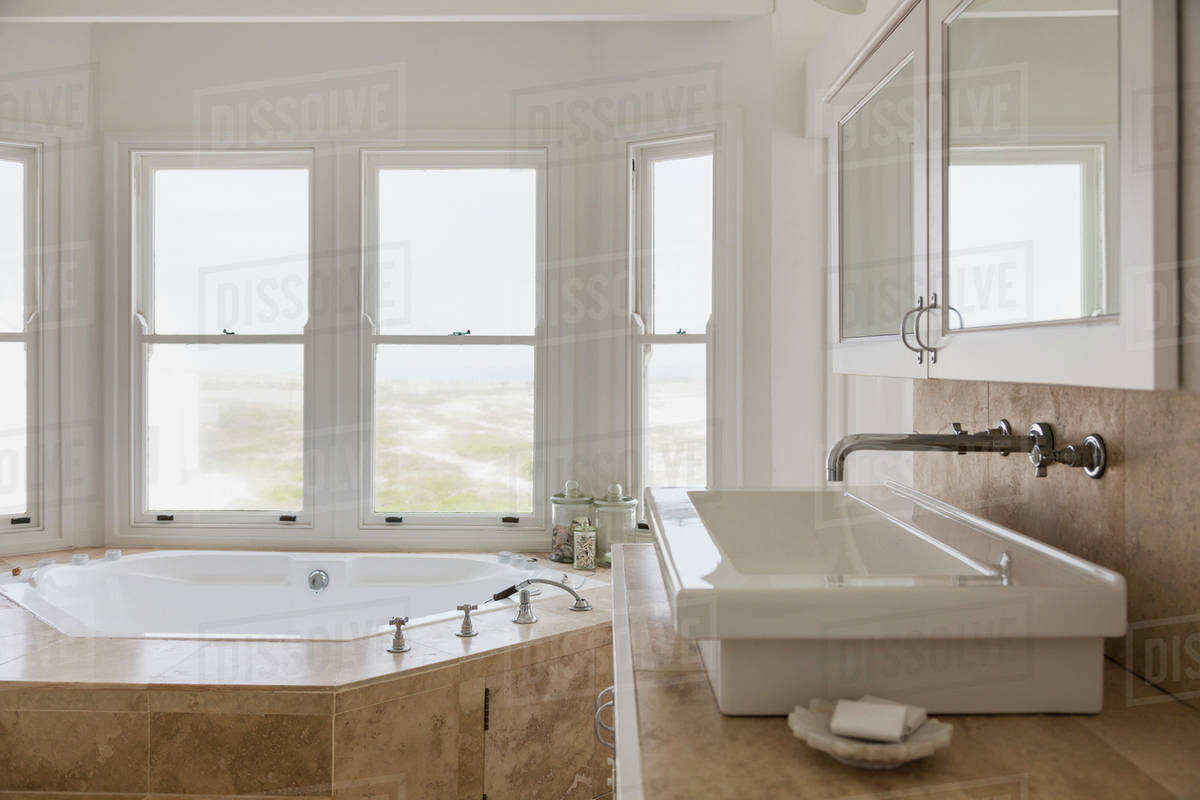 Sink and jacuzzi tub in luxury master bathroom - Stock Photo - Dissolve