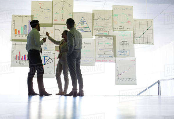 Business people discussing charts and graphs hanging in office Royalty-free stock photo