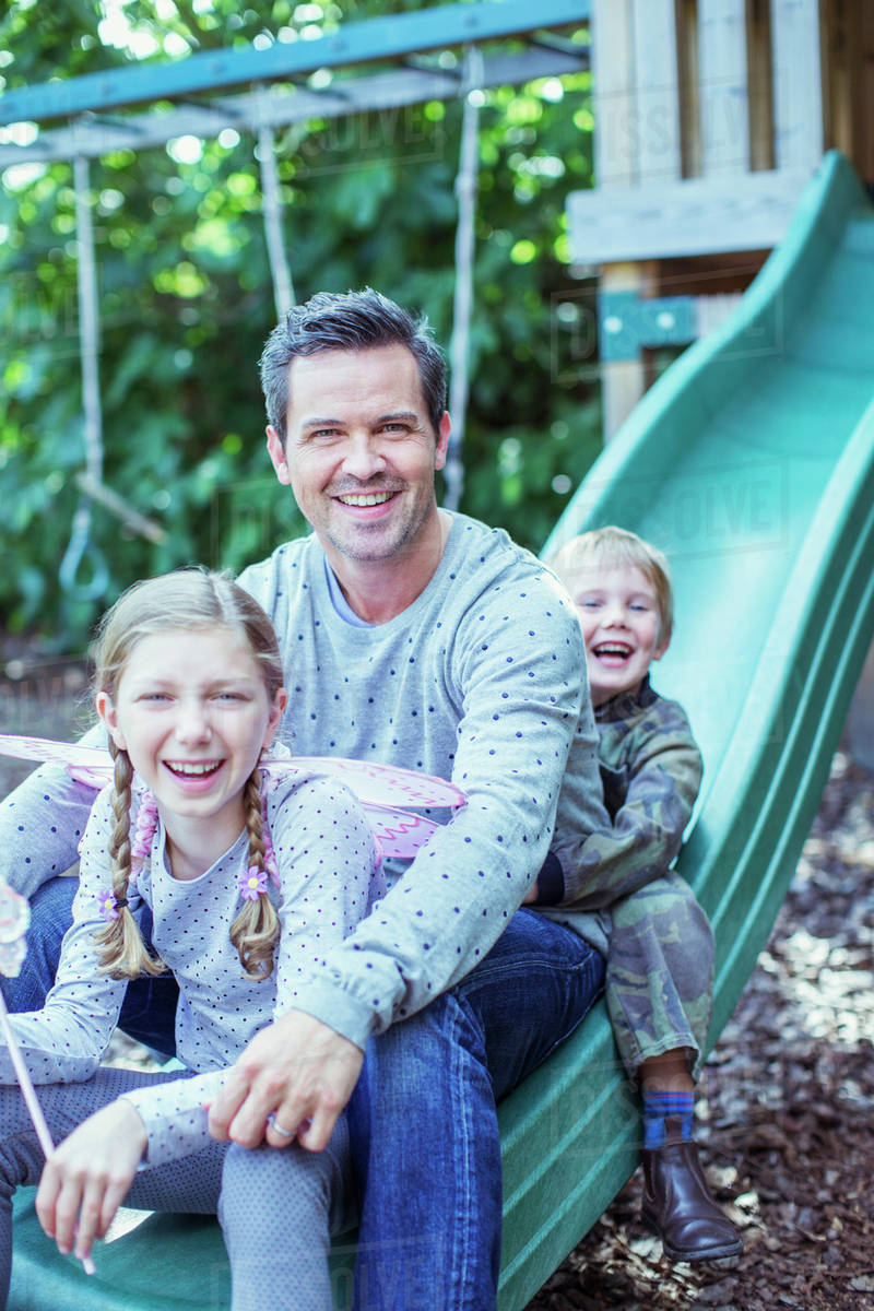 Father and children sitting on slide Royalty-free stock photo