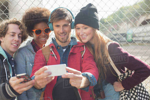 Friends taking self-portrait with camera phone outdoors Royalty-free stock photo