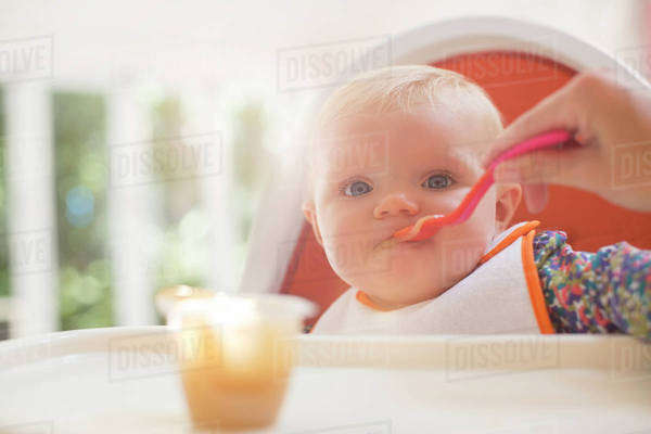 Mother feeding baby girl in high chair Royalty-free stock photo