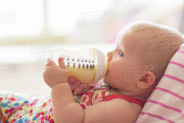 Baby girl drinking from bottle on sofa Royalty-free stock photo