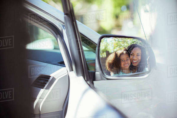 Reflection of smiling mother and daughter in side-view mirror Royalty-free stock photo