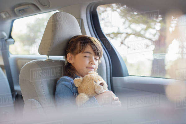 Girl with teddy bear sleeping in back seat of car Royalty-free stock photo