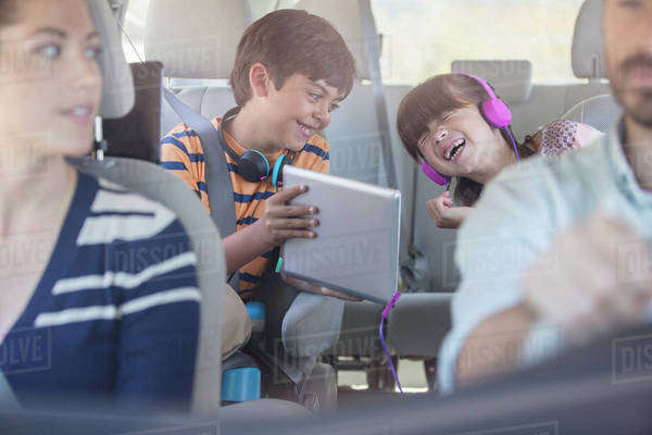 Happy brother and sister using digital tablet in back seat of car Royalty-free stock photo