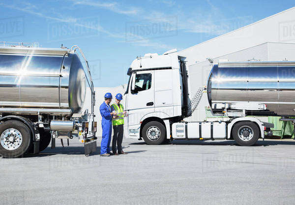Workers talking next to stainless steel milk tankers Royalty-free stock photo