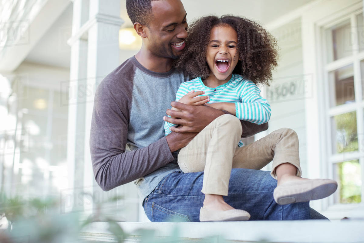 Father tickling daughter on porch Royalty-free stock photo