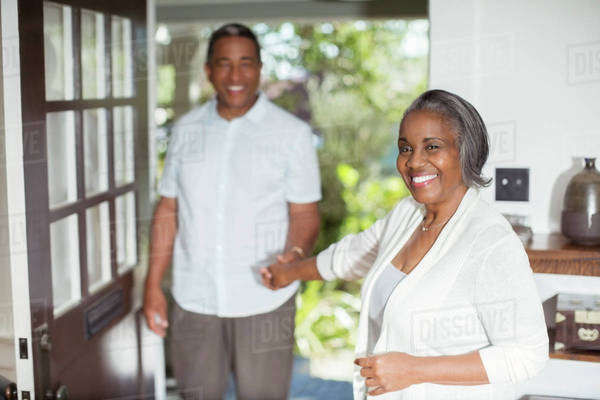 Portrait of smiling senior couple holding hands in doorway Royalty-free stock photo