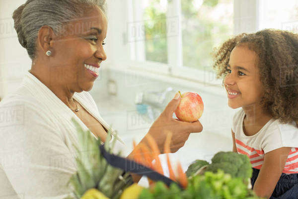 Happy grandmother giving apple to granddaughter in kitchen Royalty-free stock photo