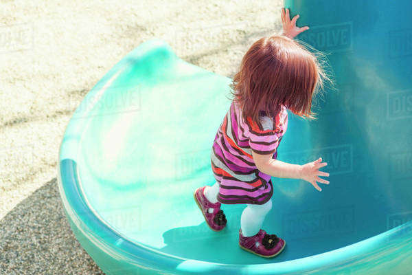 Baby girl climbing slide at playground Royalty-free stock photo