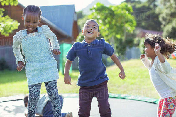 Children jumping on trampoline outdoors Royalty-free stock photo
