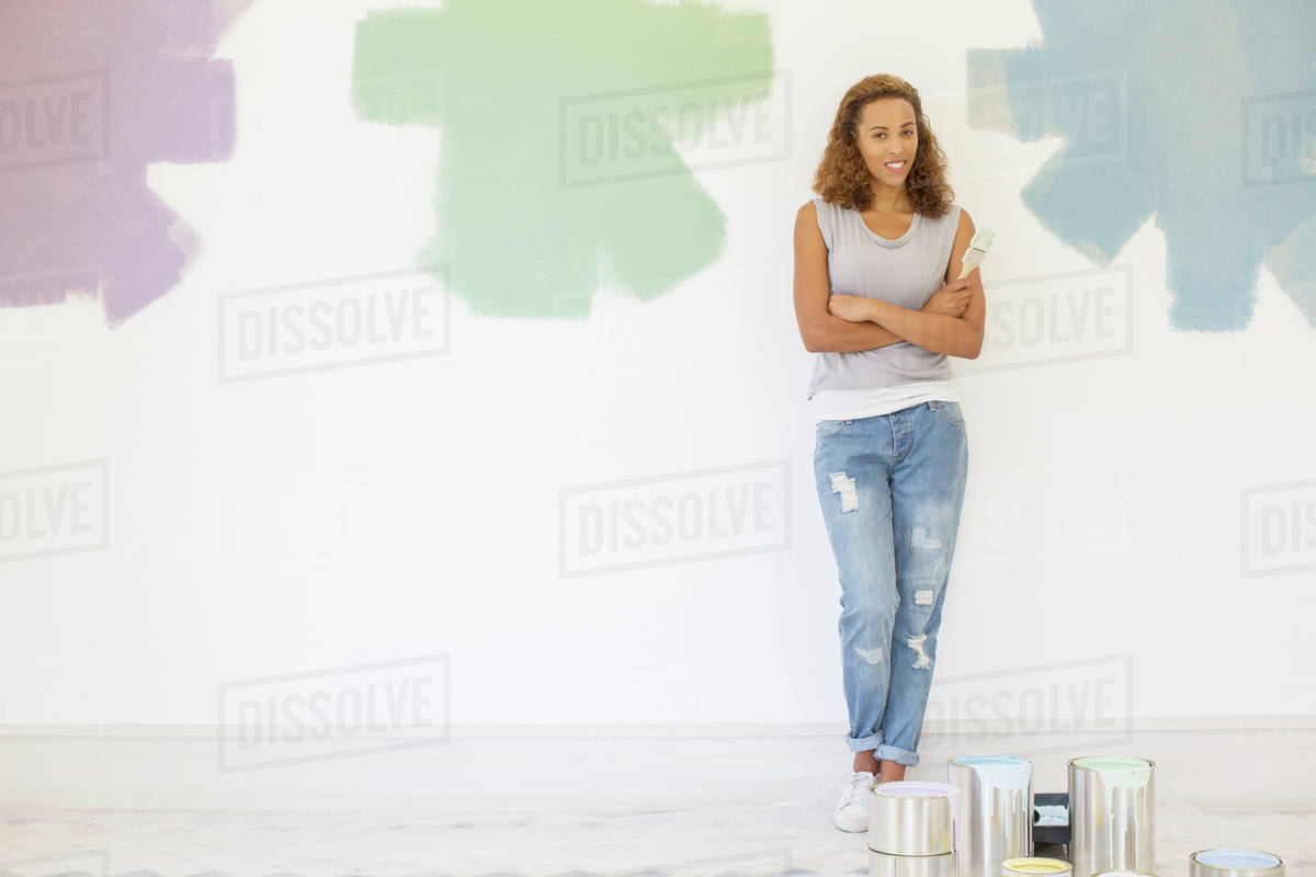 Woman Standing Between Paint Swatches On Wall