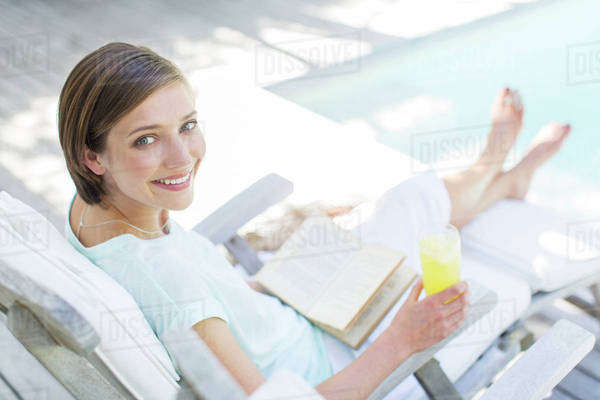 High angle view of woman reading and drinking juice by swimming pool Royalty-free stock photo