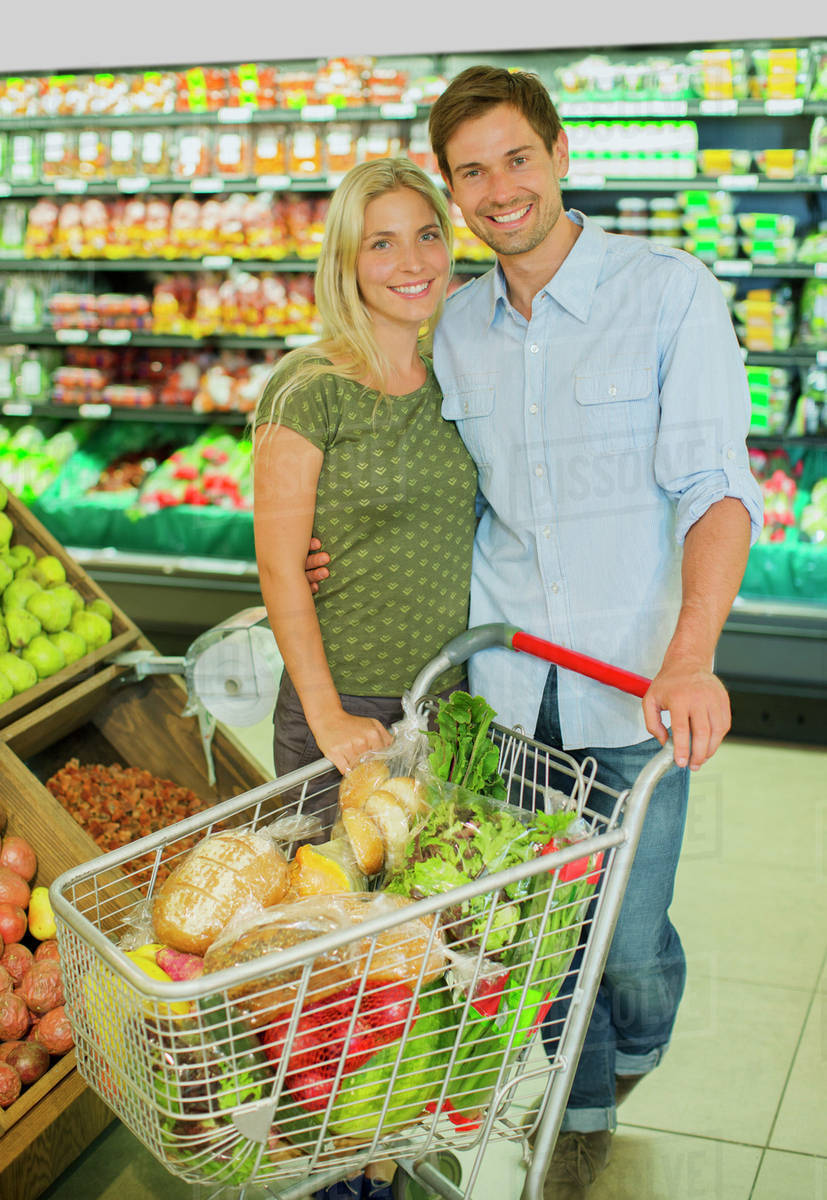 Couple Smiling With Full Shopping Cart In Grocery Store Stock Photo