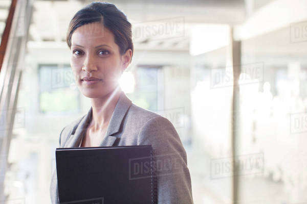 Portrait of businesswoman holding documents in office corridor Royalty-free stock photo