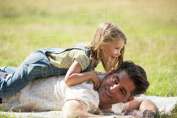 Playful daughter laying on top of father in sunny field Royalty-free stock photo