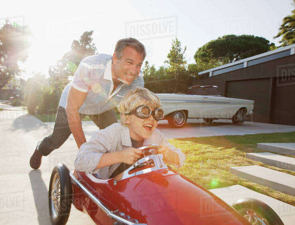 Father pushing son in go cart Royalty-free stock photo