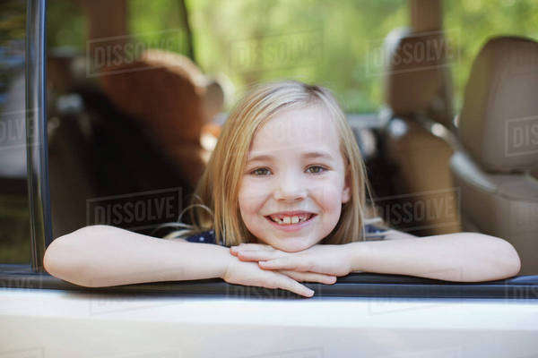 Smiling girl leaning out car window Royalty-free stock photo
