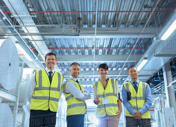 Portrait smiling workers in reflective clothing in factory Royalty-free stock photo