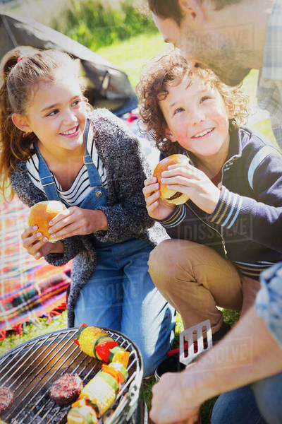 Father and kids eating hamburgers at barbecue grill Royalty-free stock photo
