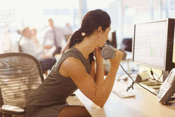 Businesswoman doing biceps curls with dumbbell and talking on telephone at computer in office Royalty-free stock photo
